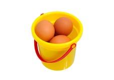 Plastic bucket with chicken eggs. Yellow plastic bucket with chicken eggs Royalty Free Stock Photos