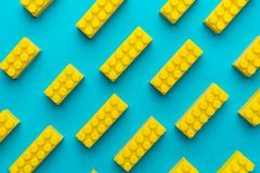 Yellow plastic building blocks background on turquoise blue. Top view of plastic blocks background. Flat lay image of toy background made with yellow building royalty free stock photography