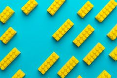 Yellow plastic building blocks on turquoise blue background with copy space. Flat lay image of yellow blocks from child constructor. Bright plastic blocks on stock photos
