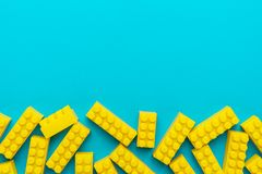 Yellow plastic building blocks on turquoise blue background with copy space. Top view of yellow plastic blocks. Flat lay image of yellow blocks from child royalty free stock images