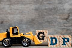 Yellow plastic bulldozer hold letter G to complete word GDP