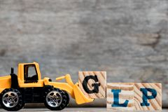 Yellow plastic bulldozer hold letter G to complete word GLP. Abbreviation Good Laboratory Practicee on wood background stock image