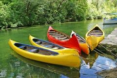 Yellow plastic canoes Stock Photos