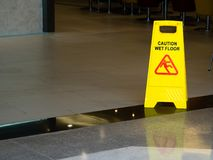Yellow plastic cone with sign showing warning of wet floor in restaurant in department store Stock Image