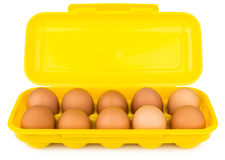 Yellow plastic container with brown chicken eggs isolated on whi Royalty Free Stock Photography