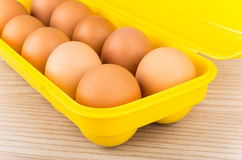 Yellow plastic container with brown chicken eggs Royalty Free Stock Images