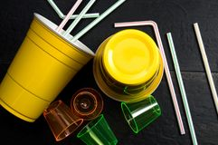 Yellow Plastic Cup, Plastic Shooter Glasses and Straws for Recycling. Horizontal stock photos