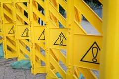 Yellow plastic fence with exclamation marks, concept of prohibition, pay attention.  Stock Images