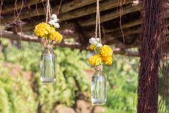 Yellow plastic flowers decorated in a bottle. Stock Photo