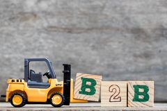 Yellow plastic forklift hold letter B to complete B2B royalty free stock image