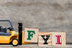 Yellow plastic forklift hold letter F to complete word FYI royalty free stock images