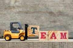 Yellow plastic forklift hold letter T to complete word TEAM. On wood background stock images
