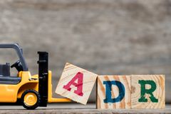 Yellow plastic forklift hold letter A to complete ADR royalty free stock images