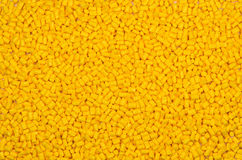 Yellow plastic granulate pellets. Yellow polymer pellets impact with glass-fiber  for injection molding Stock Image