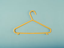 Yellow plastic hanger on a blue wall Royalty Free Stock Images