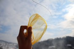 Yellow plastic mesh in the hand. With sky and snow in the background royalty free stock photo