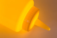 Yellow plastic mustard bottle clloseup with a glowing light Royalty Free Stock Photography