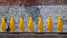 Yellow plastic penguins in a row Stock Photo