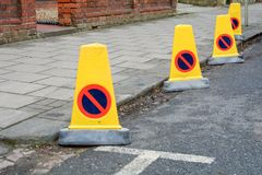 Yellow plastic police bollards at edge of road. Restricting parking Royalty Free Stock Photos