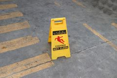 Yellow plastic sign with red symbol of slip and black text of caution wet floor on the floor. The sign of care taken to avoid danger or mistakes stock photography