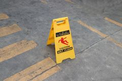 Yellow plastic sign with red symbol of slip and black text of caution wet floor on the floor. The sign of care taken to avoid danger or mistakes Stock Images