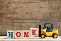 Yellow plastic toy forklift hold letter block E to word home royalty free stock image