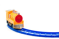 Yellow plastic train toy on blue railway. Isolated white background Royalty Free Stock Photos
