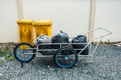 Yellow plastic trash bin against building wall. And black bag of rubbish Royalty Free Stock Photos