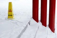 Yellow plastic wet floor sign on snowed floor. Stock Images