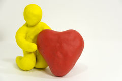 Yellow plasticine man holding in hands red heart, white backgrou Royalty Free Stock Images