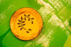 Yellow plate. Antique yellow empty plate on a green vintage table stock images