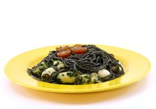 Yellow plate with black pasta and squid Stock Photo