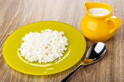 Yellow plate with defatted cottage cheese, jug with yogurt, spoon on table stock photography