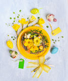 Yellow plate with easter eggs, nest with daffodils flowers and holiday decor Royalty Free Stock Photography
