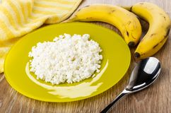 Yellow plate with grainy cottage cheese, napkin, bananas, spoon on wooden table royalty free stock images
