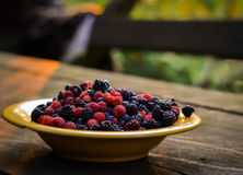 Yellow plate with raspberries, blackberries, blueberries Stock Photography