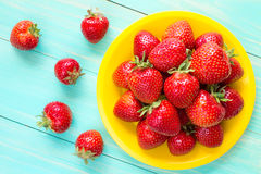 Yellow plate with red strawberries. Royalty Free Stock Images