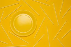 Yellow plate on a yellow background and yellow tubes for drinks, a concept of dishes. Or a holiday royalty free stock photo