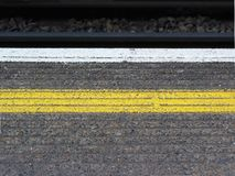 Yellow platform line. Yellow saftey line painted on a train station platform in london, england Royalty Free Stock Images