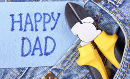 Yellow pliers on jeans pocket. Happy Dad`s Day greeting paper. Simple way to congratulate father Royalty Free Stock Images