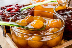 Yellow Plum jam in glass bowl  with spoon and various marmalades. Breakfast concept Stock Photo