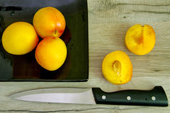 Yellow plums on a balck plate Stock Photo