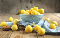 Yellow plums in blue bowl. Selective focus Royalty Free Stock Photography