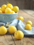 Yellow plums in blue bowl Stock Images