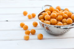 Yellow plums in a colander on a white board Royalty Free Stock Photo