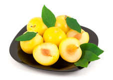 Yellow plums with leaves on a black plate royalty free stock image