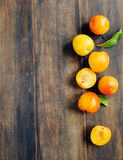 Yellow plums on wooden background Stock Photos