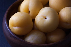Yellow plums in wooden bowl Stock Photography