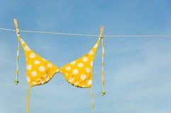 Yellow Polka Dot Bikini. An itsy-bitsy teeny weeny yellow polka dot bikini hanging on a clothesline with copy space Stock Image