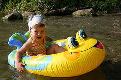 Yellow ponton. Small girl plays in water to sunny day stock photos